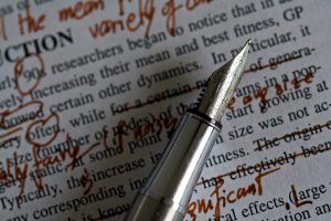 A nib pen resting on paper with text and red editing marks.